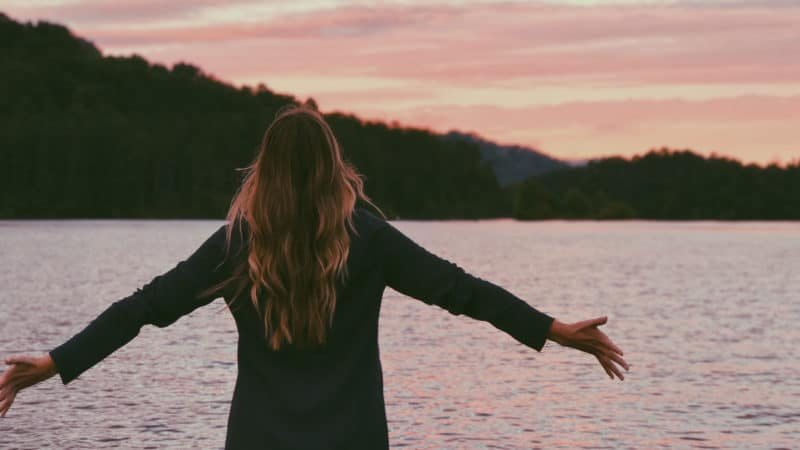 Woman stands in front of lake at sunset with her arms outstretched