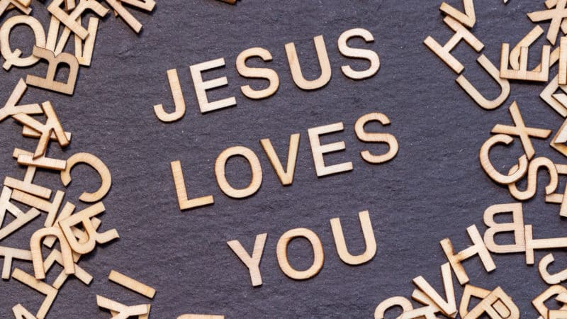 wooden letters JESUS LOVES YOU on dark slate background