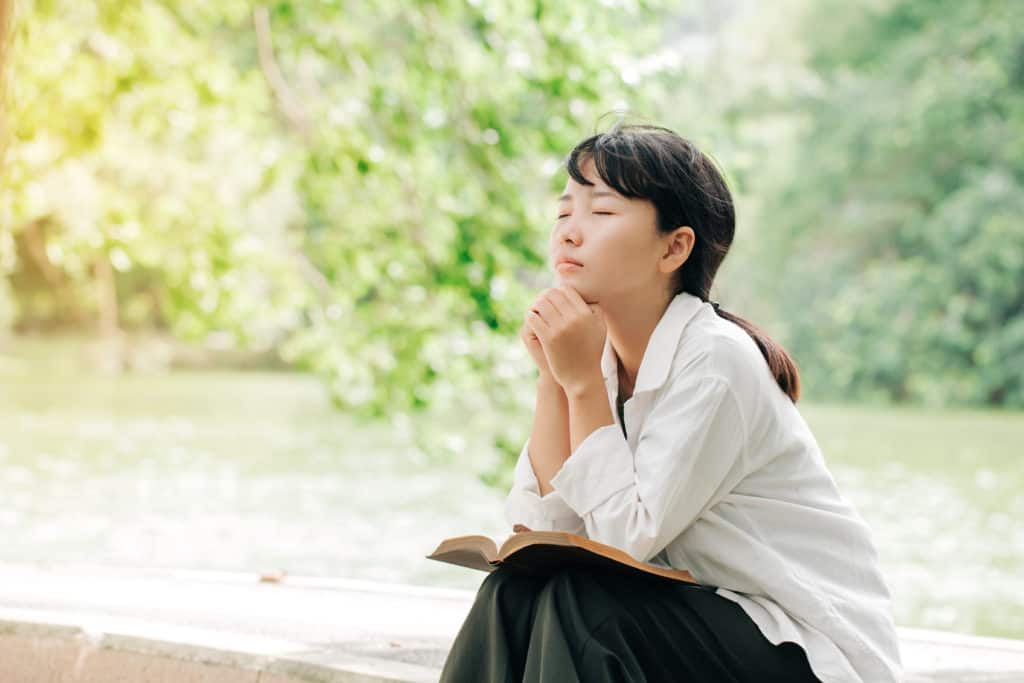 Woman praying in the morning on nature background.Hands folded in prayer on a Bible