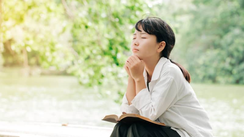 Woman praying in the morning on nature background. Hands folded in prayer on a Bible as we learn nature of humanity