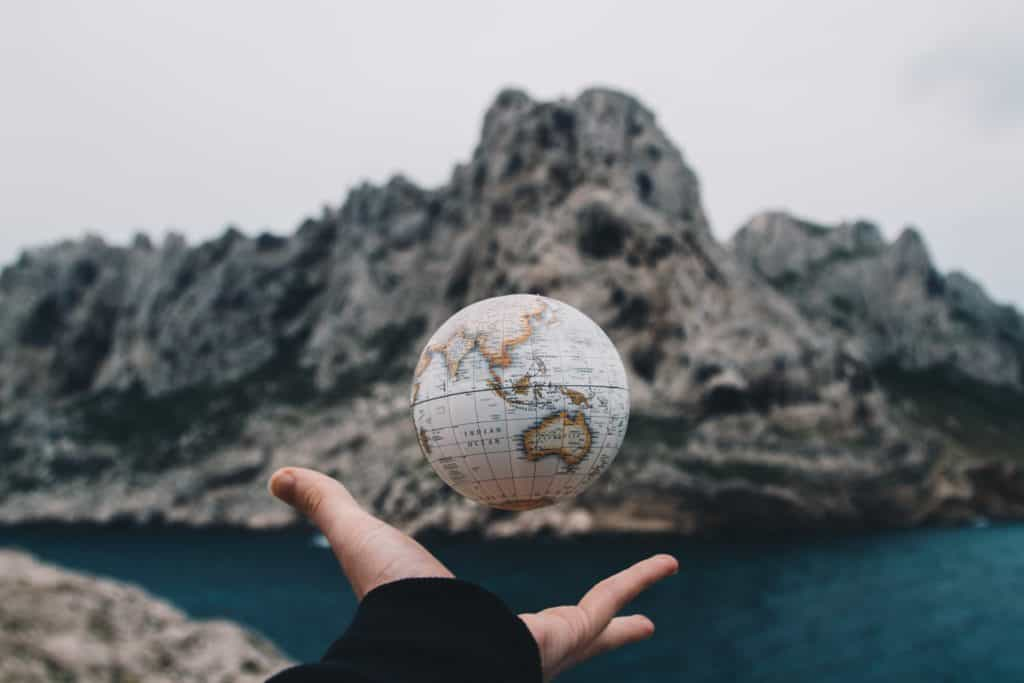 A person tossing a globe above their hand.