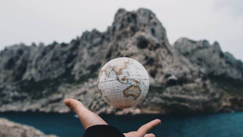 a person tossing a small globe above their hand with ocean rock formations and an inlet blurred in the distance