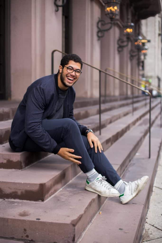 A happy young man sitting on steps outside of a building.