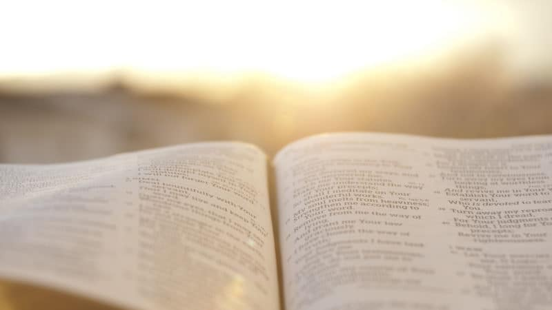 Open Bible with bright sunset in the background.