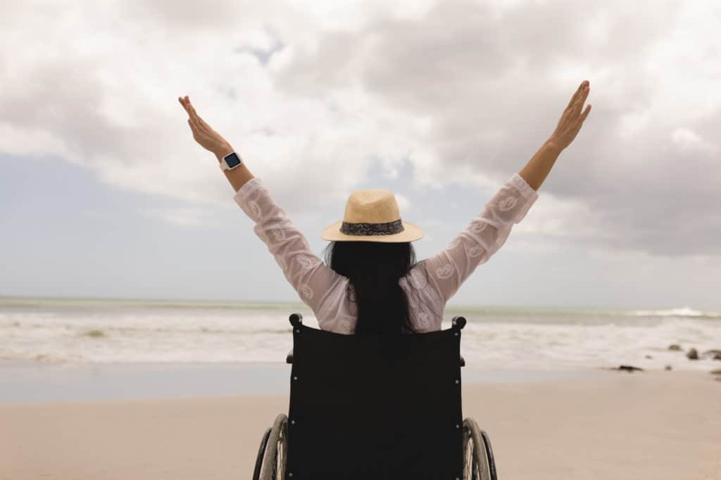 Rear view of a woman in a wheel chair with arms stretched out at beach in the sunshine