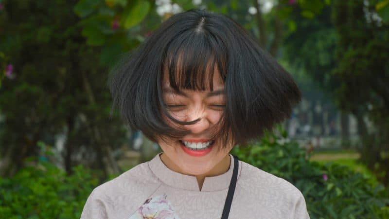 a happy woman with a big smile standing outdoors with shoulder length black hair blowing in the breeze