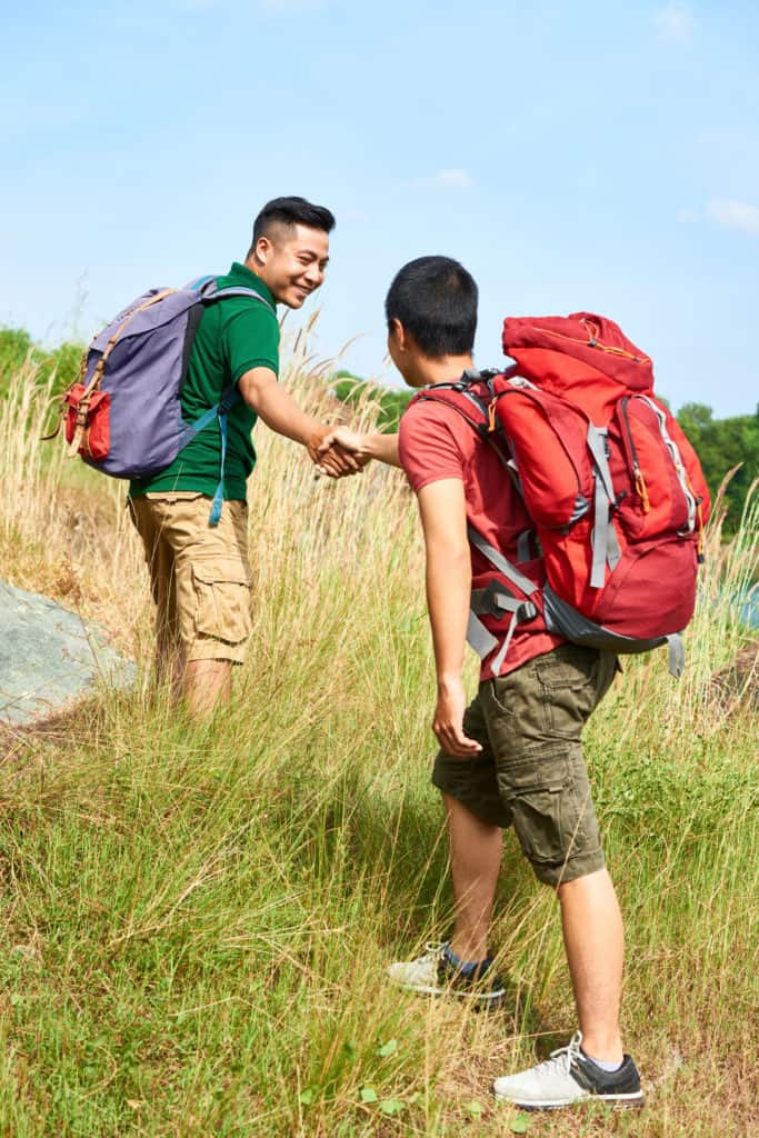 Smiling hiker outstretching hand to help his friend