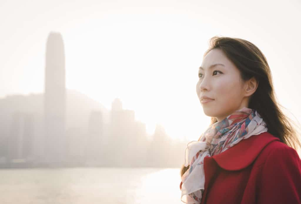 A woman standing with a skyline in background.