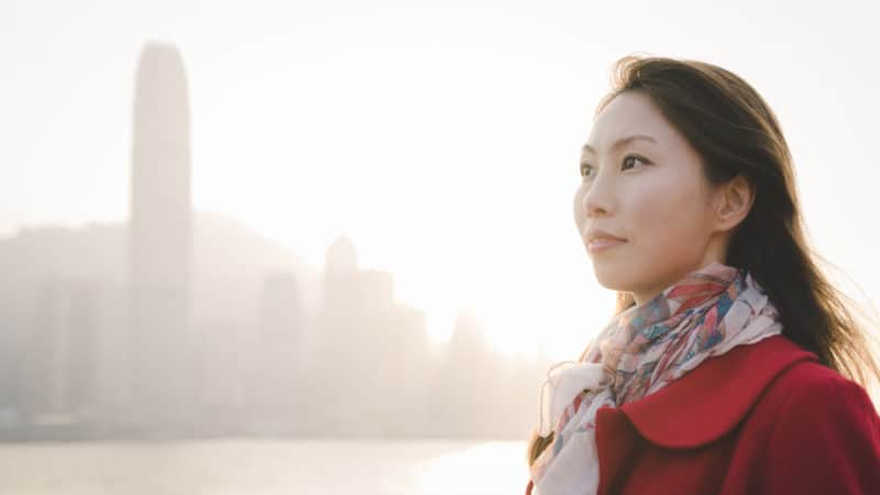 Woman in a red wool coat and scarf standing with a skyline in the background thinking about the gift of salvation