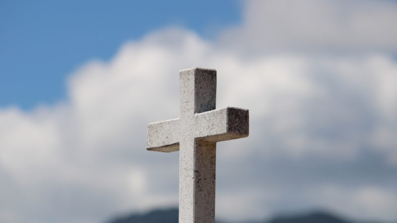 Stone Cross with clouds behind.