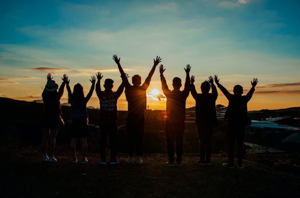Group of people looking at the sunset with arms raised.