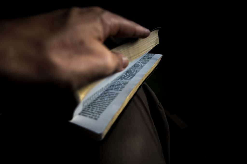 A hand opening a Bible.