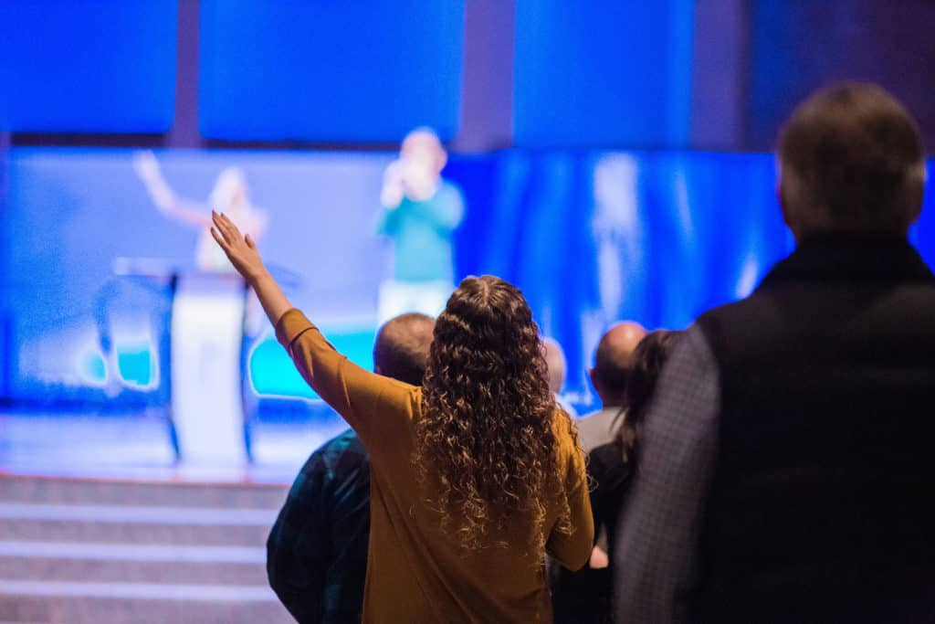 A woman at church with her hand raised in praise