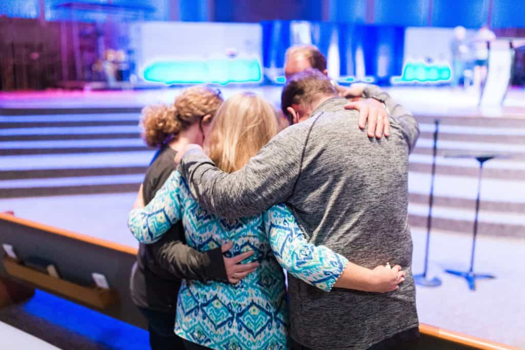 Four people praying together at church.