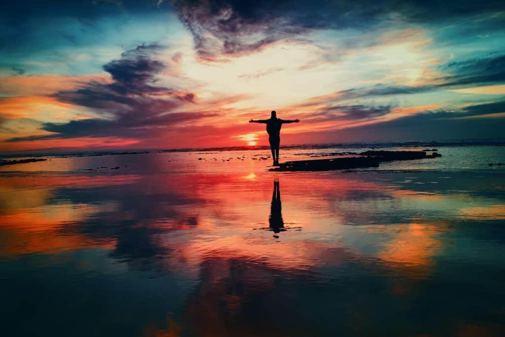 A person standing on the beach with arms outstretched at sunset.