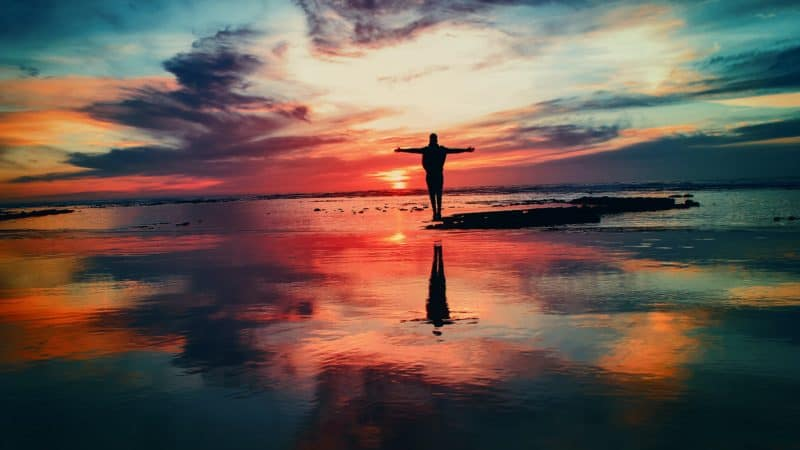 silhouette of a woman on the beach with arms outstretched in front of a vibrant red sunset