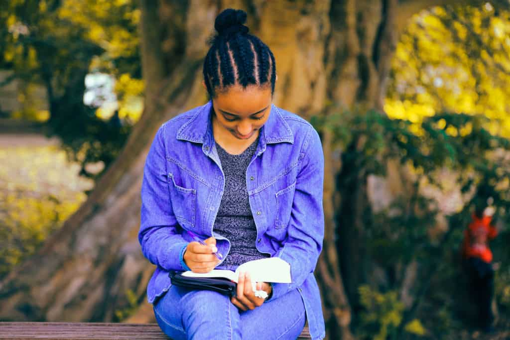 A young girl sitting outside and studying her Bible
