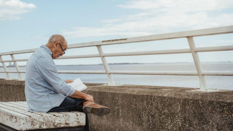 Man reading the Bible on a bench outside
