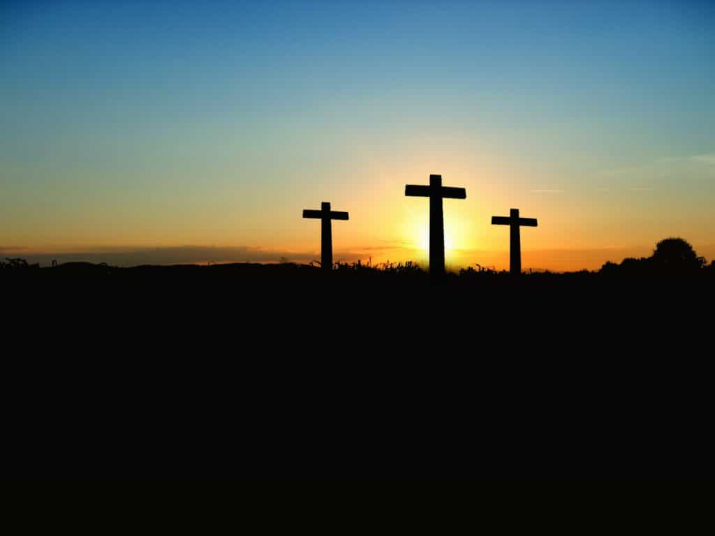 Three crosses with the sun setting behind them.