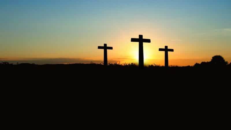 Three crosses with the sun setting behind them as we study how Jesus redeemed humanity by His death on the cross