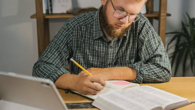 Man studying the Bible and taking notes.
