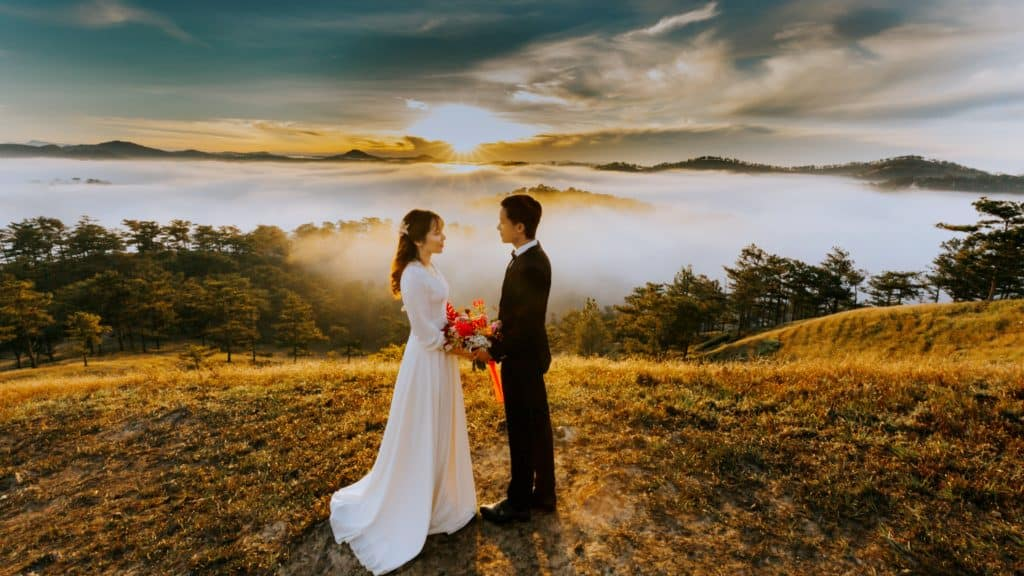 An asian couple getting married in front of a beautiful landscape.