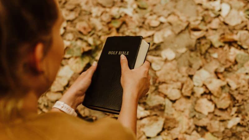 A woman holding a Bible outside as we learn of gift of power of choice from God and choose to follow Him