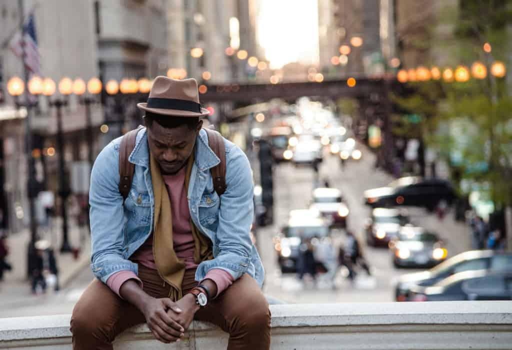A sad man sitting on a bridge over a busy street.