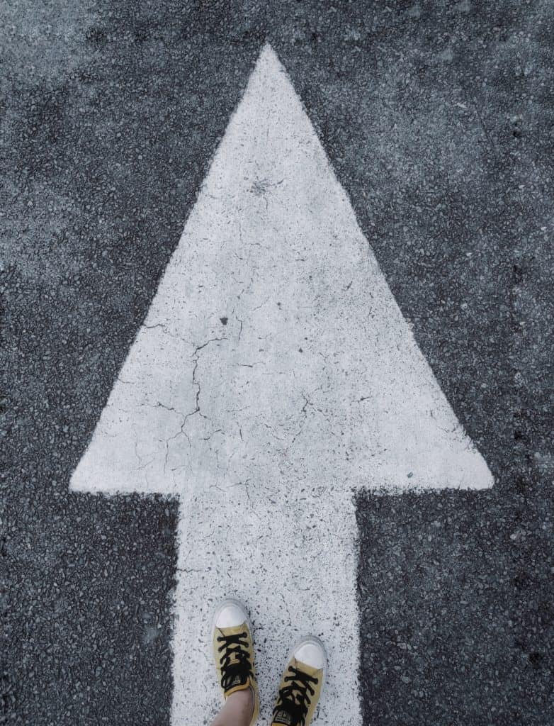 An arrow on the road with feet pointing forward.