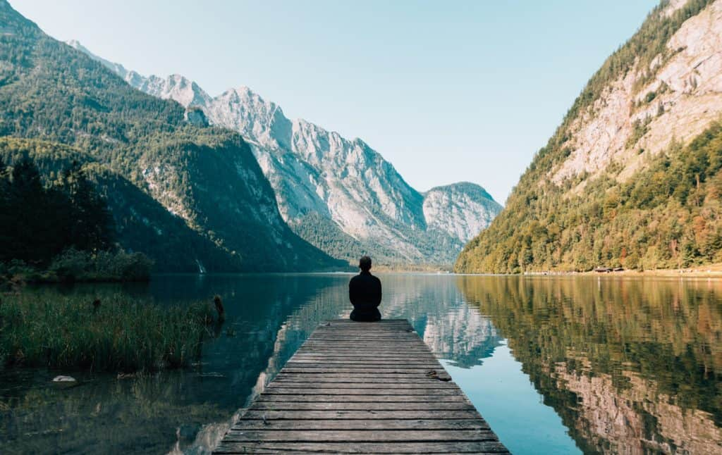 A man sitting on a dock looking at a beautiful mountain landscape.