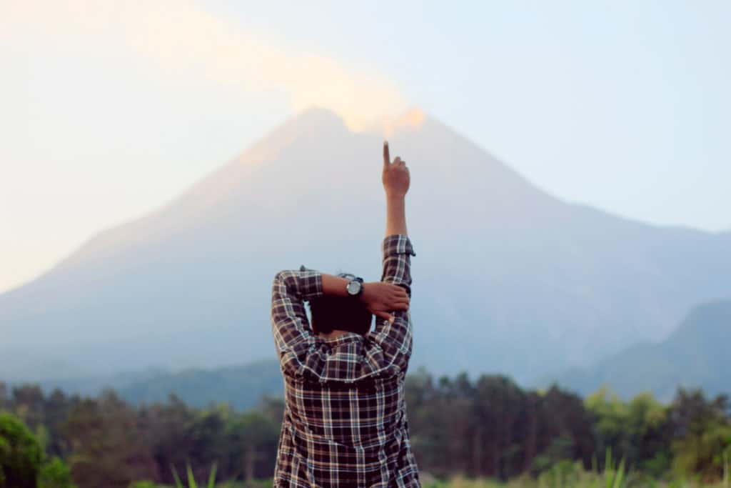 A man standing in front of a mountain with this hand raised and finger pointed towards the sky.