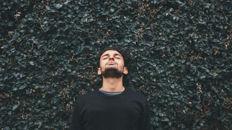 a man with his eyes closed and face tilted up standing in front of an ivy wall contemplating his new life in Christ