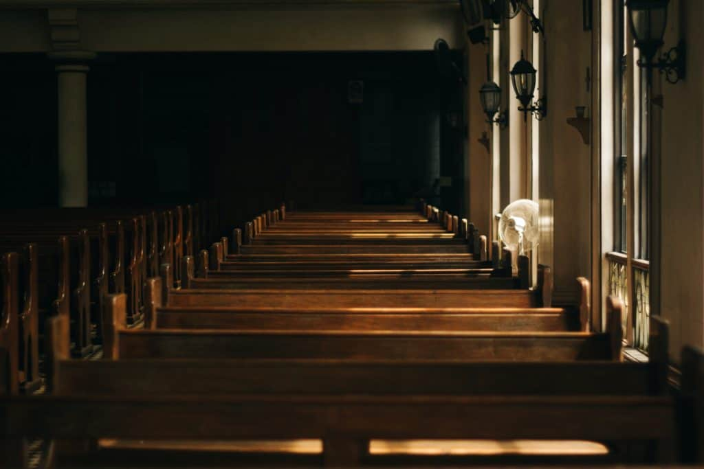 Church interiors with the sun shining through the windows onto the pews.