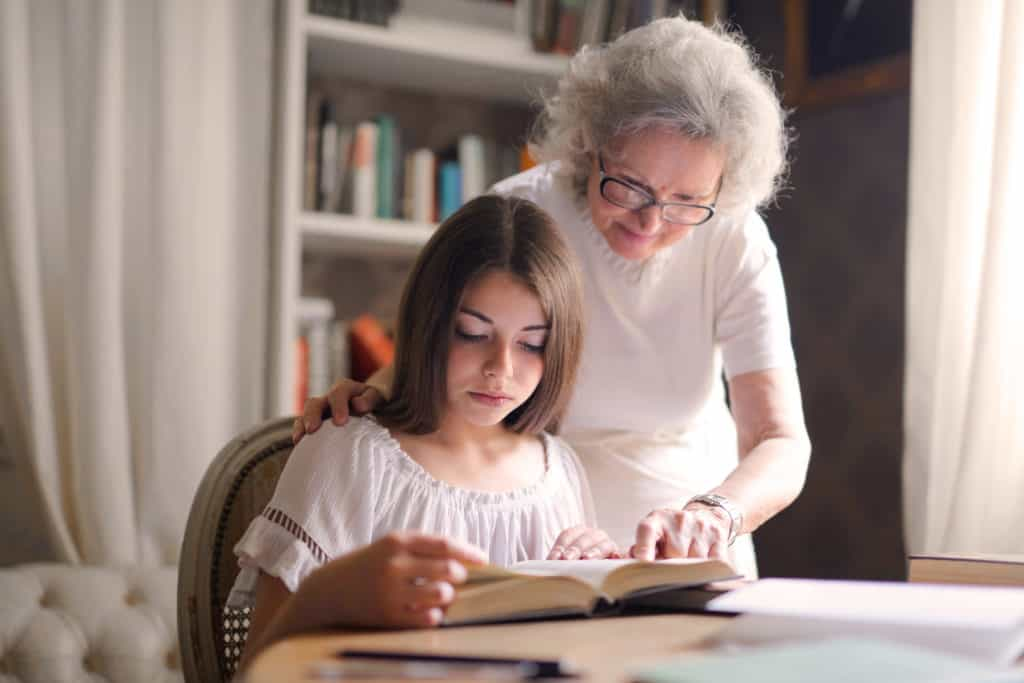 An older woman helping a young girl read the Bible.
