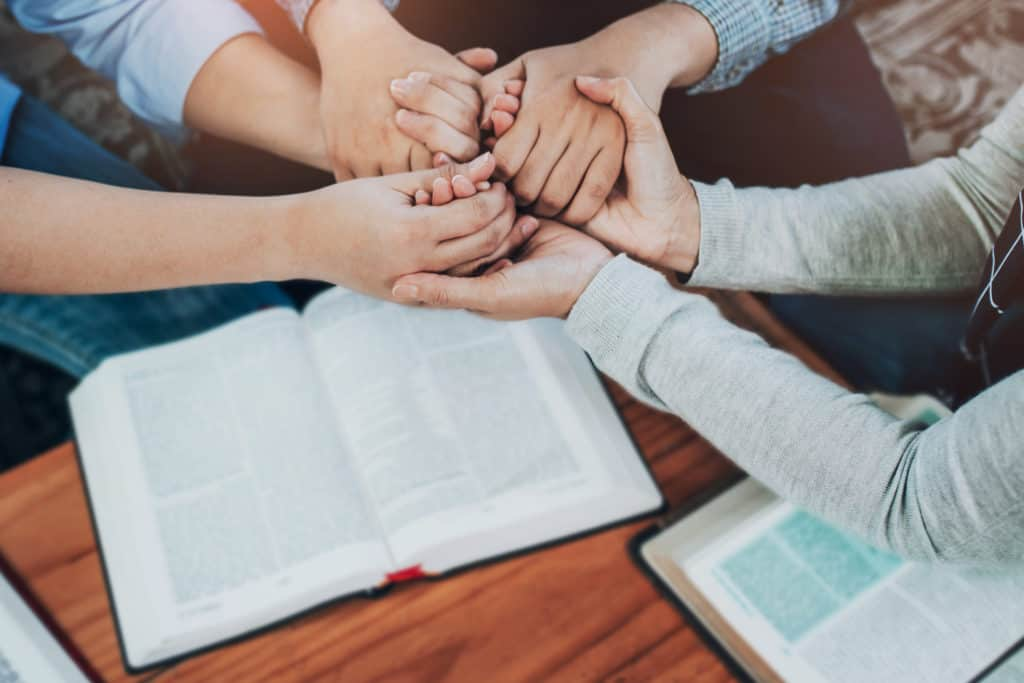 Christian friends joining hand and pray together over Bible on wooden table