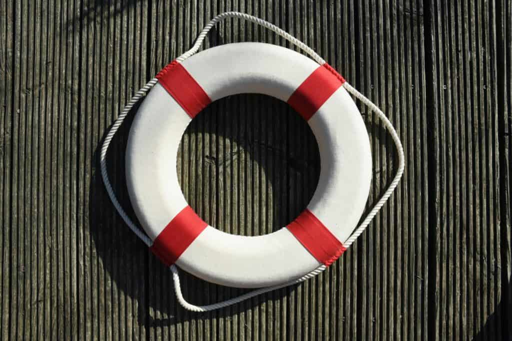 overhead view of a round red and white life preserver on wooden surface