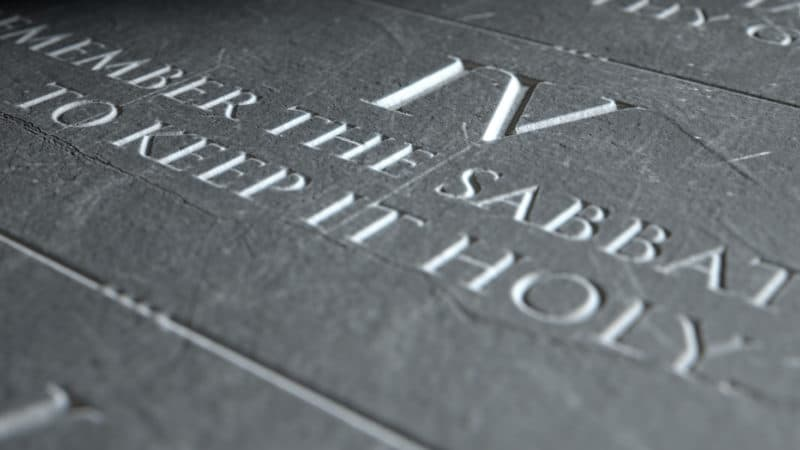 closeup of the ten commandments etched in a stone tablet highlighting the fourth