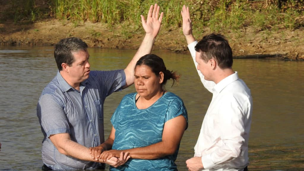 A woman being baptized in a river.