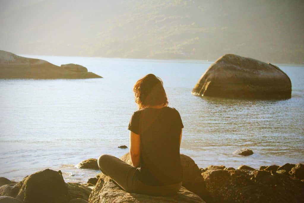 A woman sitting on a rock by a body of water at sunset.