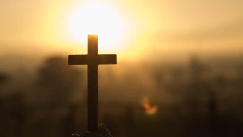The cross in the sunrise colored sky background