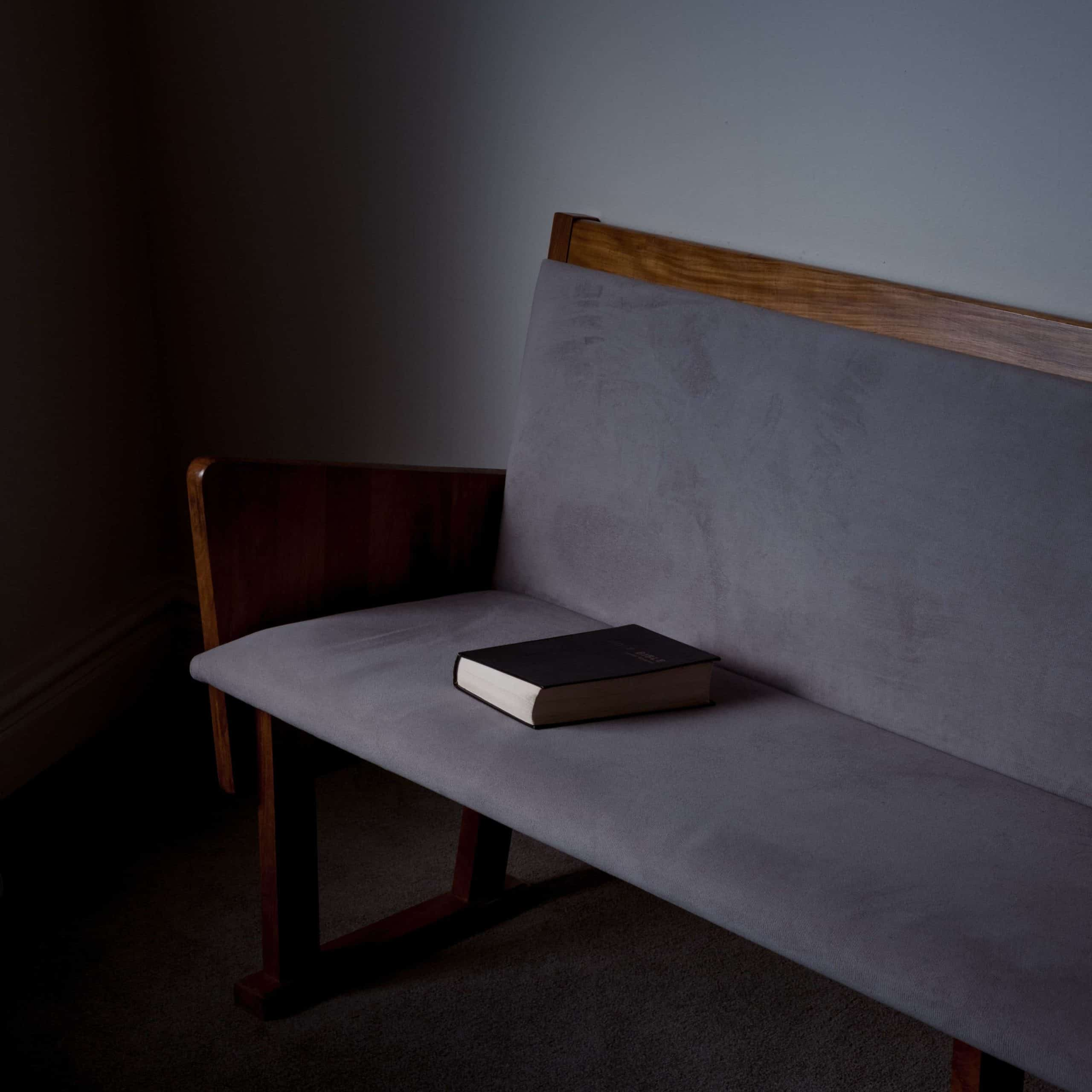 A Bible laying on a church pew.