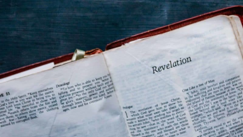 The Bible open to the book of Revelation on a black table as it mentions of many end time prophecies and of Jesus' return