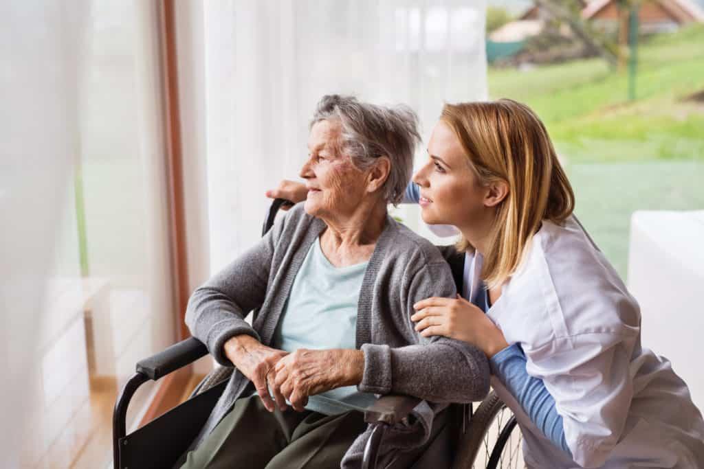 A nurse talking to an elderly woman in a wheelchair.