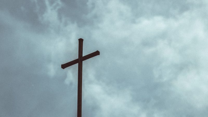 The cross against a cloudy sky as we study about the death of Jesus on the Cross of Calvary for our sins