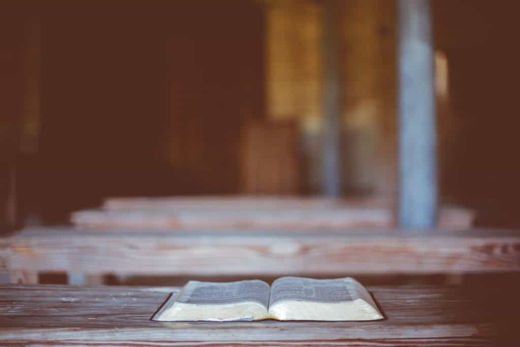 A Bible laying open on a wooden table.
