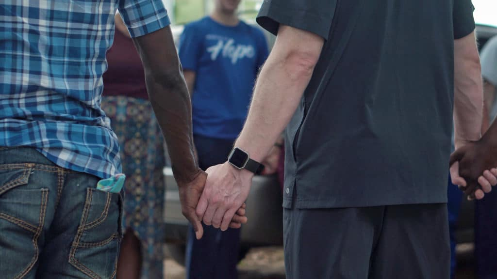 A group holding hands in prayer. A close up of their hands.