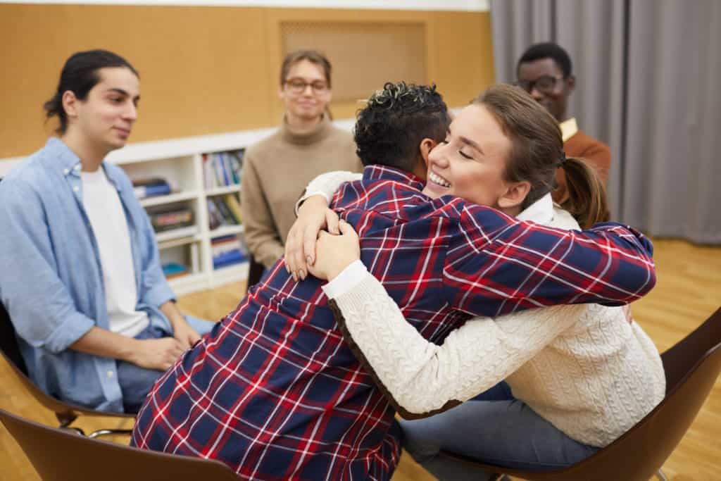 Portrait of two young people hugging in support group meeting.