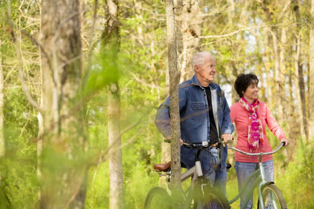 Active senior couple outside riding bikes in a wooded park area of their neighborhood.