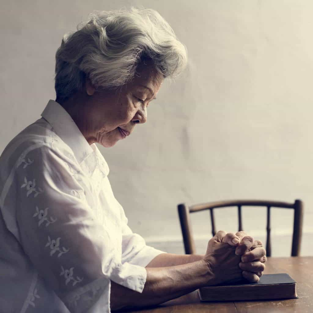 A woman praying with her Bible at a table as we pray that God will help us to understand the prophecies in the Bible