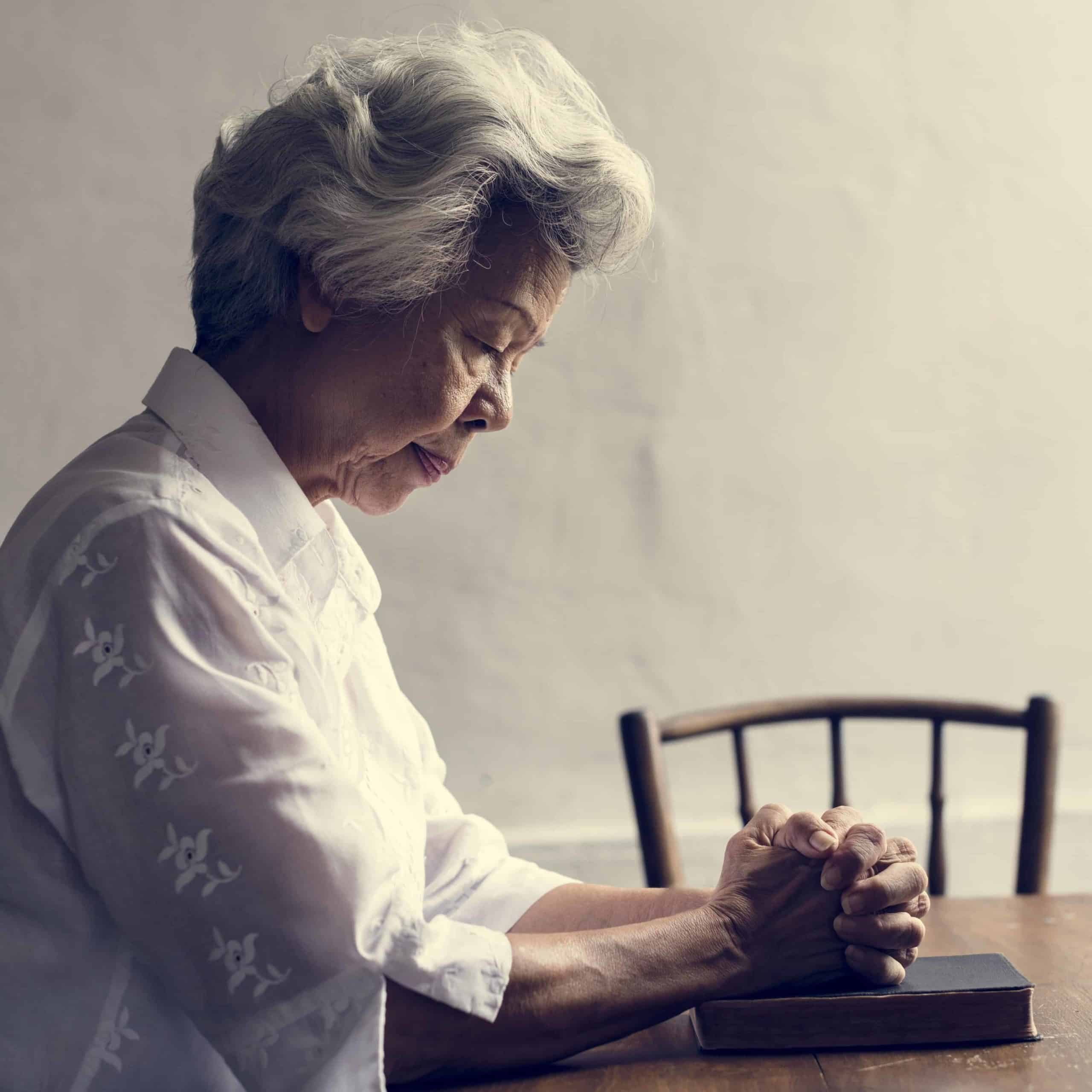 A woman praying with her Bible at a table.